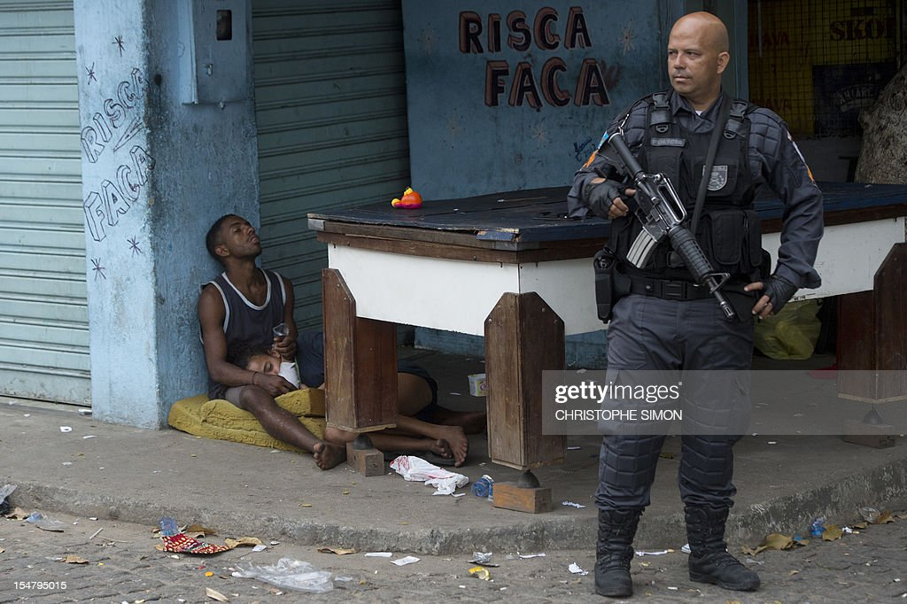 A couple Crack's addicted sleep next to a paramilitary police officer at Parque Uniao slum before a social workers and police joint operation to take addicts out of the streets, in Rio de Janeiro, Brazil on October 26, 2012. AFP PHOTO/Christophe Simon