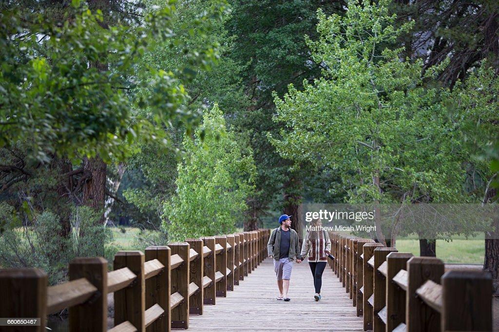A couple cross a swing bridge in Yosemite.