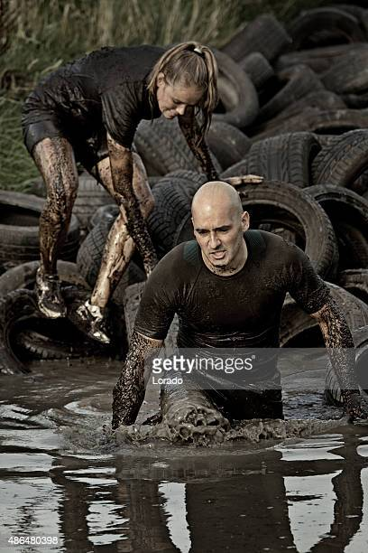 couple crossing muddy canal with tyres