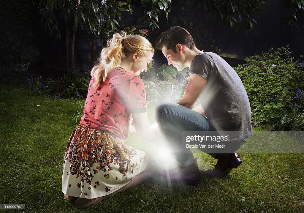 Couple crouched, looking at shining light.