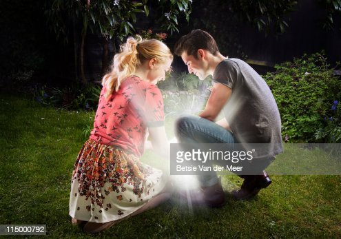 Couple crouched, looking at shining light. : Stock Photo