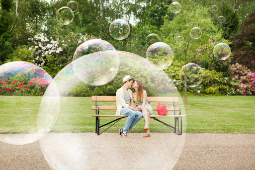 Couple cuddling on bench, surrounded by bubbles.