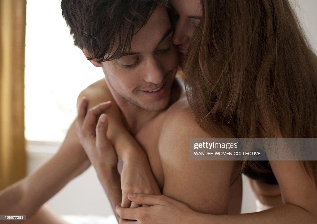 Couple cuddling sitting on bed : Stock Photo