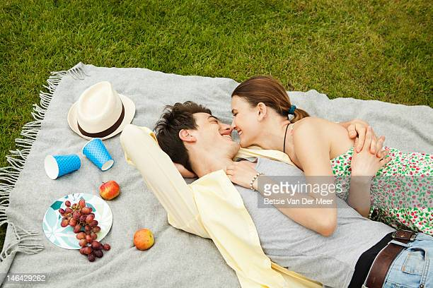 couple cuddling up on picnic blanket in park.