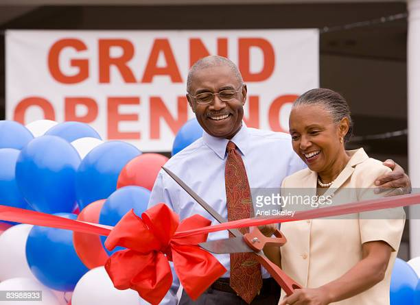 Couple Cutting Ribbon at Grand Opening Celebration