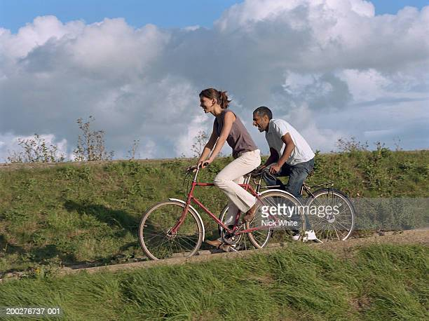 Couple cycling along path by grassy bank