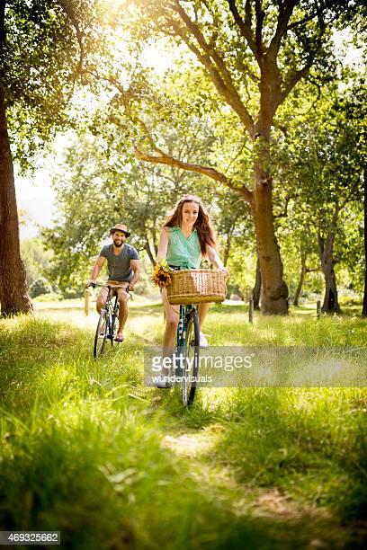 Felizmente Casal Ciclismo através de um parque de Verão