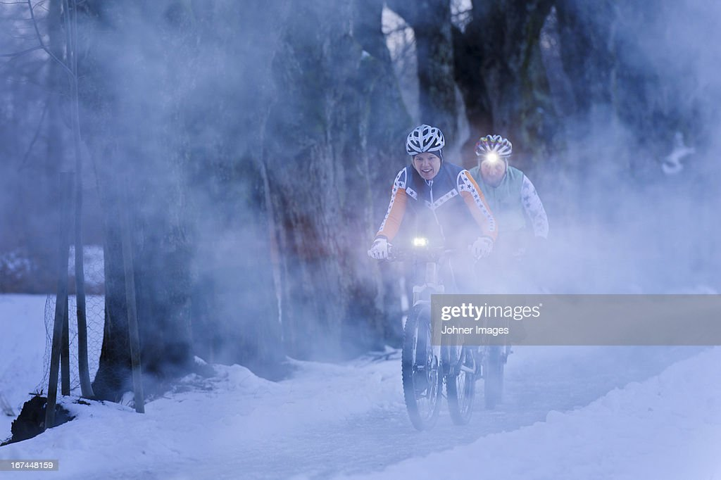 Couple cycling in fog : Stock Photo