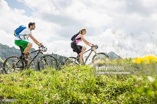 Couple cycling through field, Tyrol, Austria