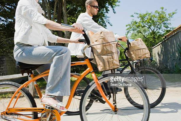 Couple cycling with groceries in baskets