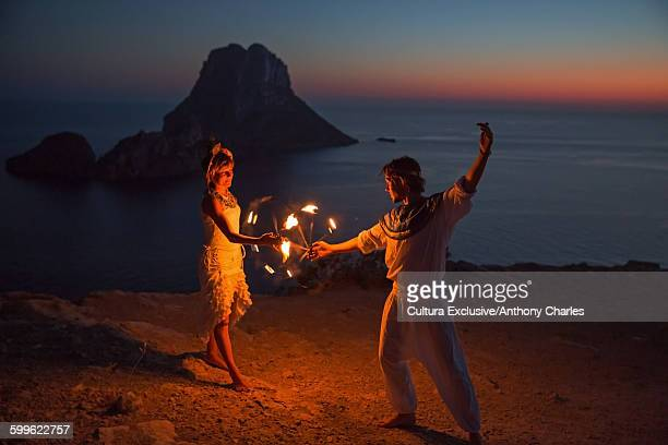 Couple dance with fire sunset, Ibiza, Es Vedra rock in the background