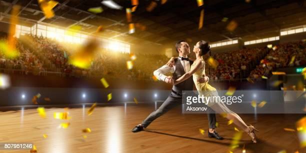 Danseurs de couple ardemment exécutent la danse de l'Amérique latine sur une grande scène professionnelle avec feux d'artifice de sparkle