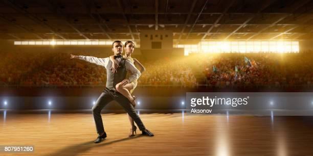 Danseurs de couple ardemment exécutent la danse de l'Amérique latine sur une grande scène professionnelle