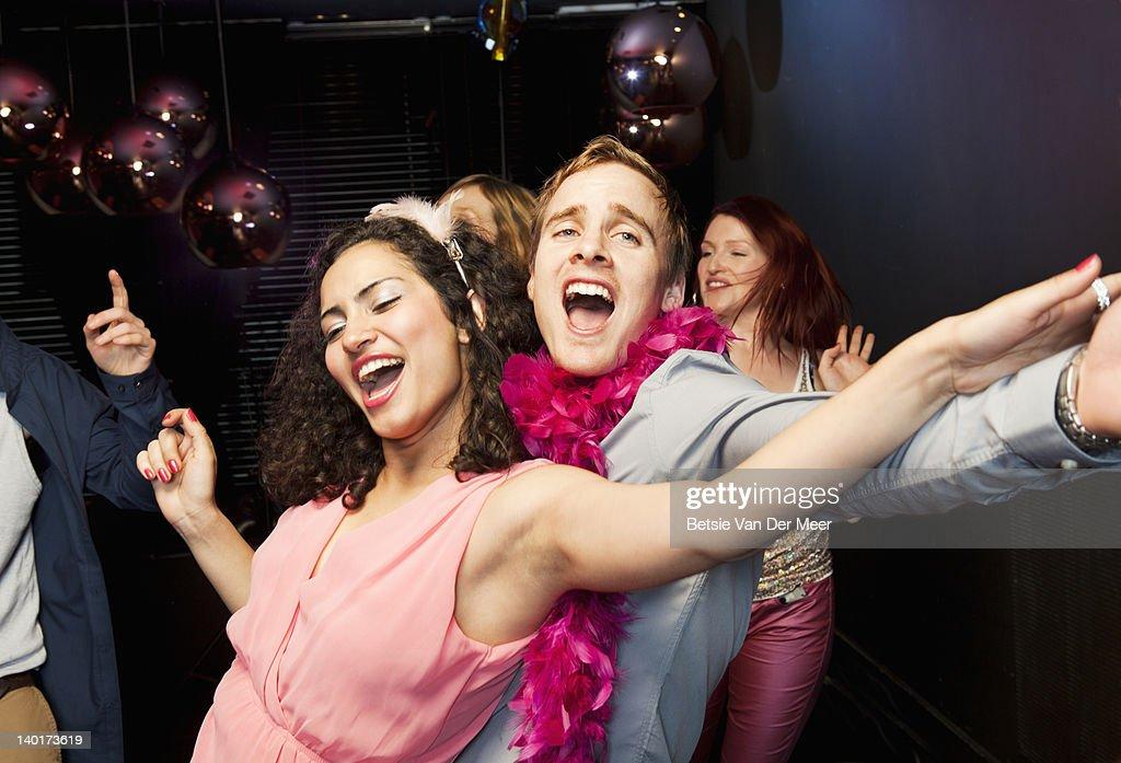 Couple dancing and singing on dancefloor. : Stock Photo