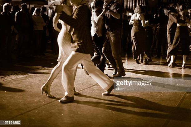 Couple dancing Argentine Tango outdoors at night.