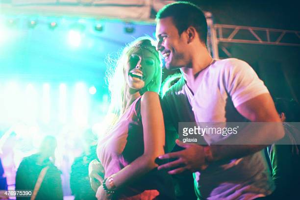 Couple dancing at concert party.