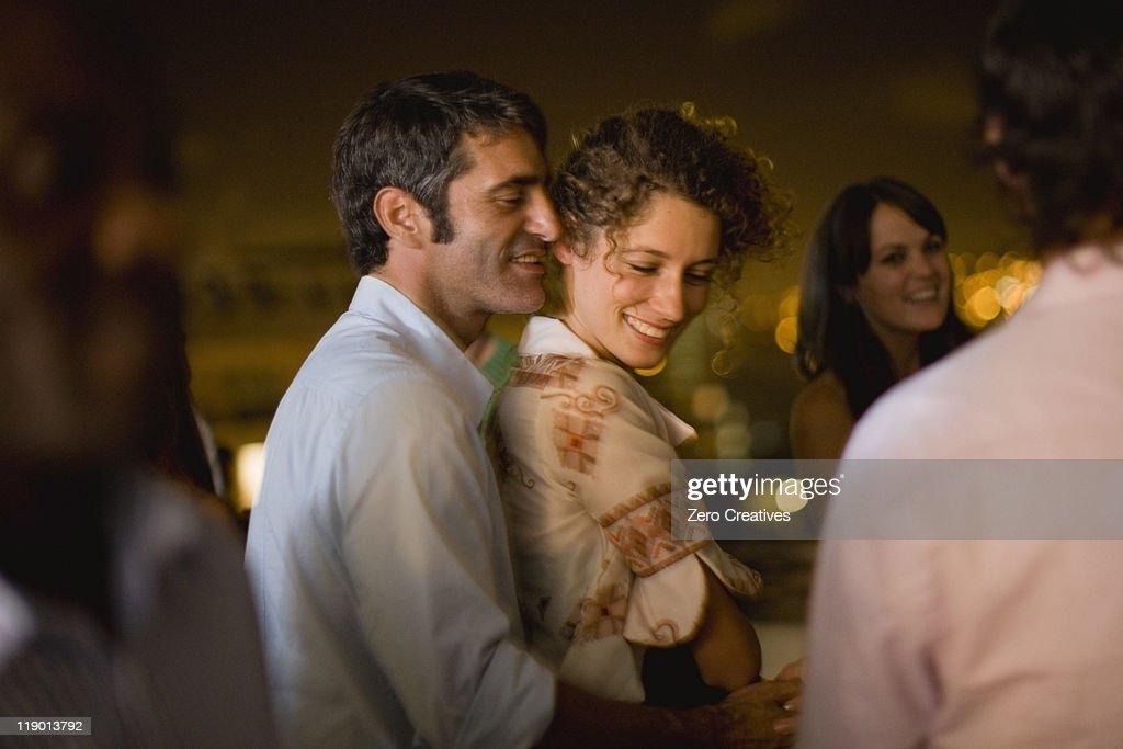 Couple dancing at party at night