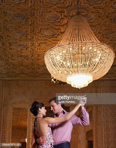 Couple dancing beneath chandelier, low angle