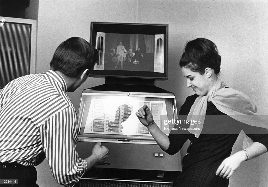 A couple dancing by a jukeboxcumtelevision or Scopitone in a coffee bar Groovy