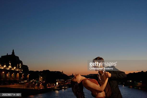 Couple dancing by river at dusk, woman leaning back supported by man