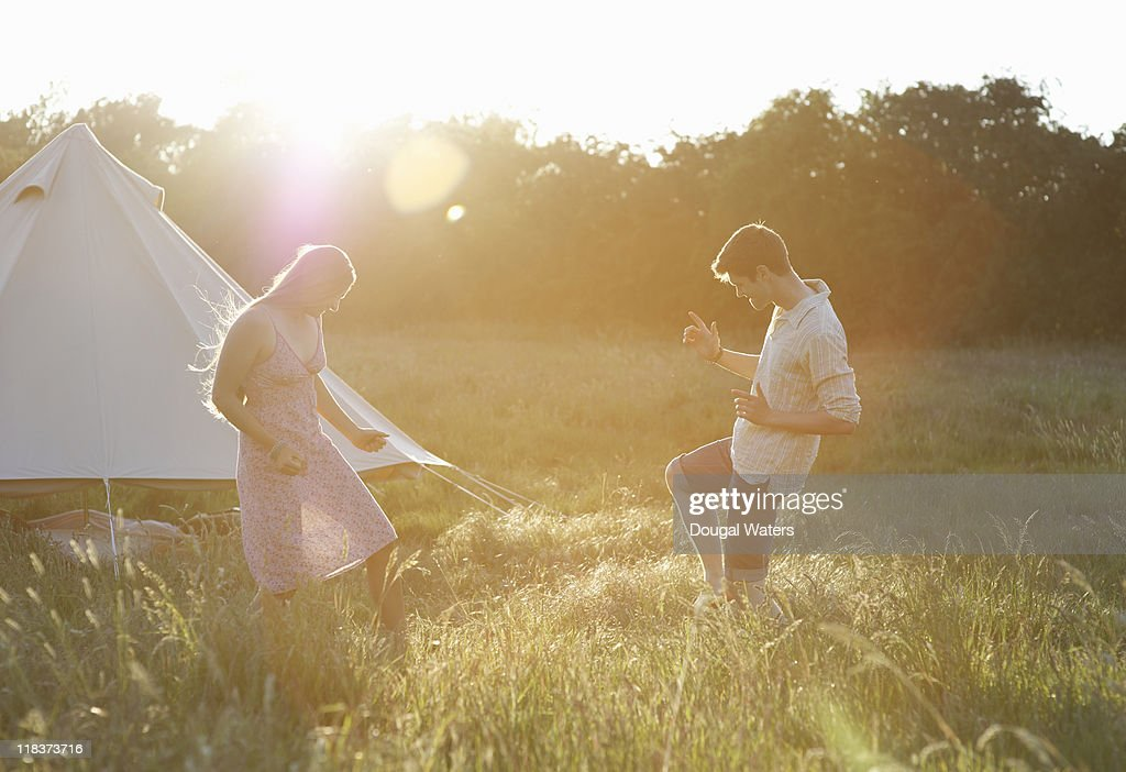 Couple dancing in meadow at sunset. : Stock Photo