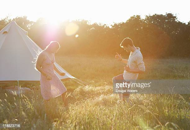 Couple dancing in meadow at sunset.