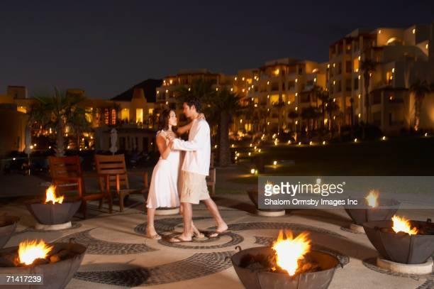 Couple dancing outdoors at resort hotel at night