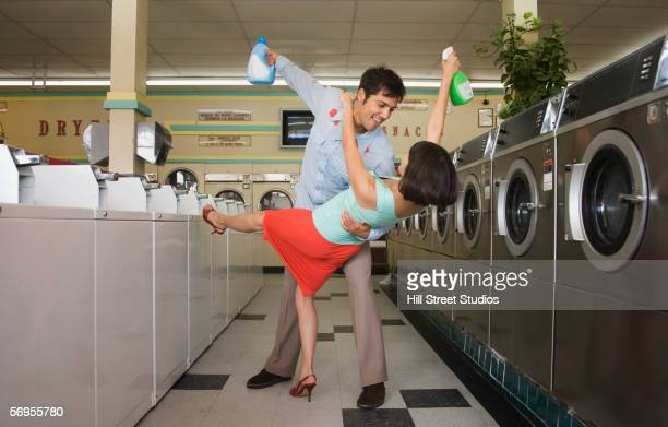 Couple dancing with soap in launderette