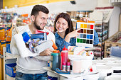 Young loving couple deciding on the best color scheme at a paint supplies store. Focus on both persons