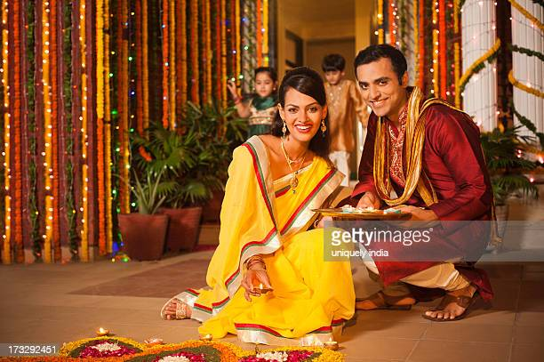 Couple decorating rangoli with oil lamps on Diwali