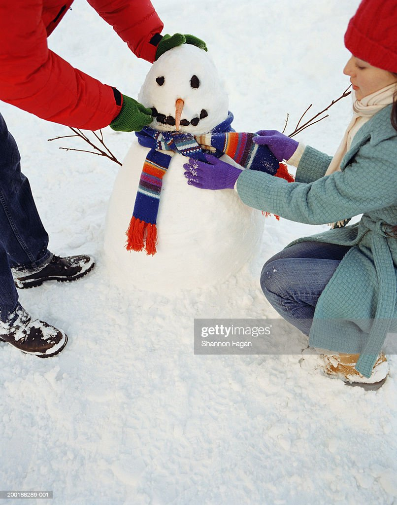 Couple decorating snowman : Stock Photo
