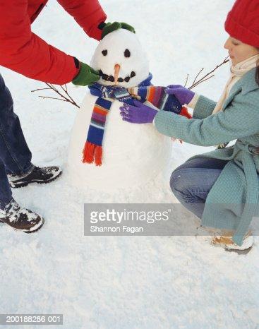 Couple decorating snowman : Stock Photo