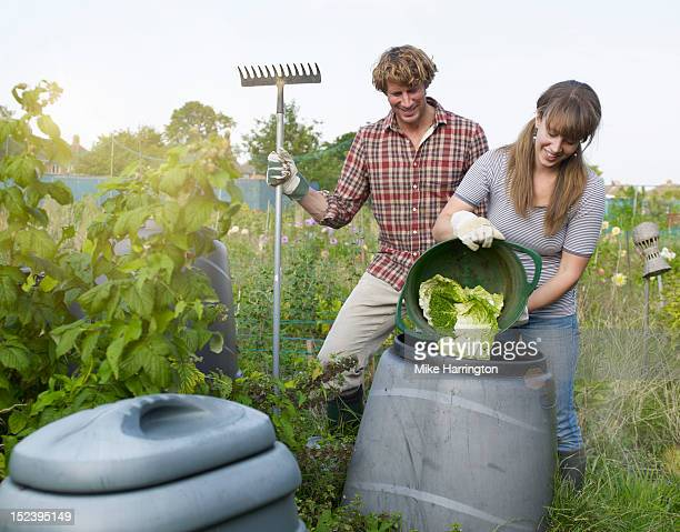 Couple depositing waste into compost bin