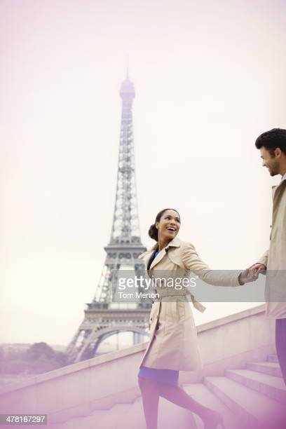 Couple descending stairs by Eiffel Tower, Paris, France
