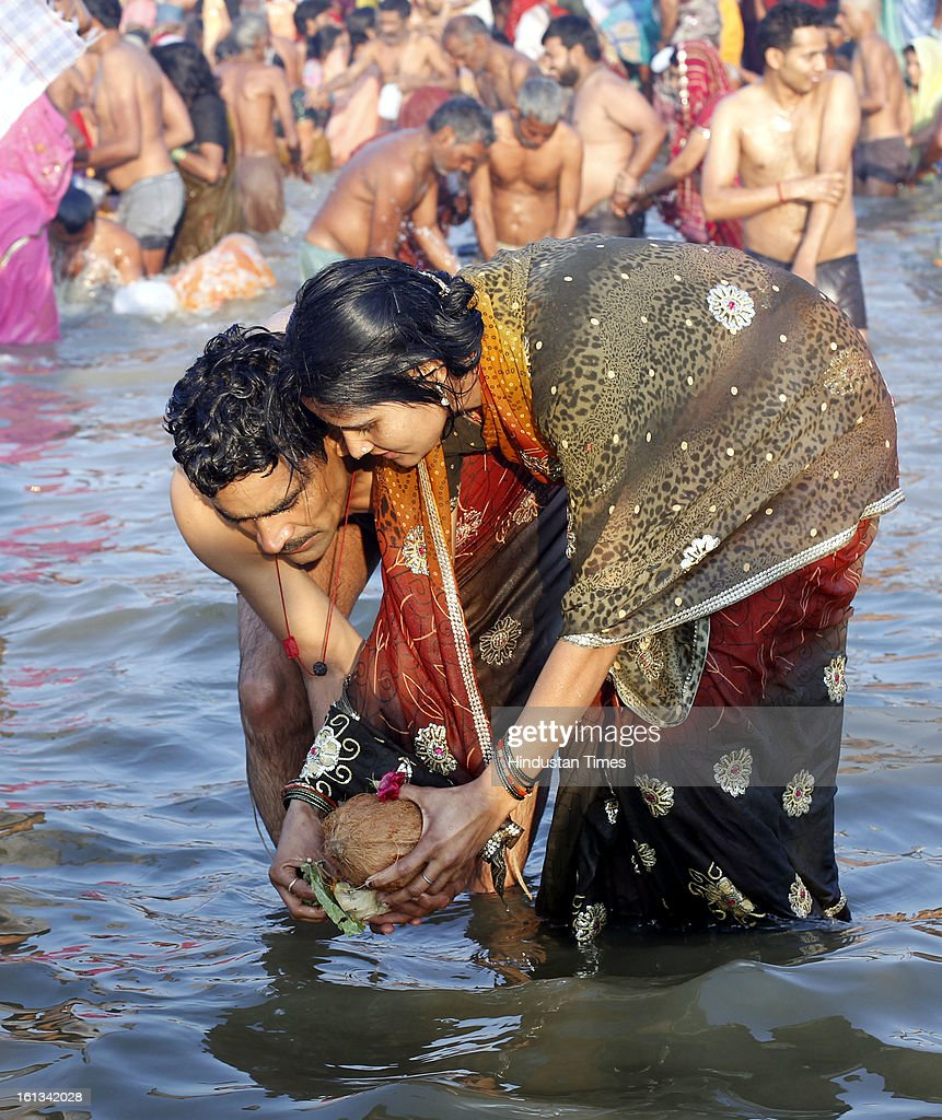 A couple devotee releases an offering into the Sangam confluence of river Ganga, Yamnuna and mythical Saraswati on the occasion of Mauni Amawasya on February 10, 2013 in Allahabad, India. Tens of millions of Hindus gathered Sunday for a holy bath in India's sacred river Ganges on the most auspicious day of the world's largest religious festival.