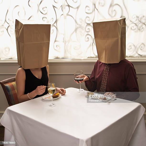 Couple dining in a restaurant with paper bags over heads