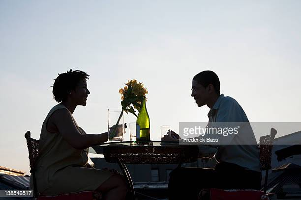 A couple dining on a rooftop terrace at sunset