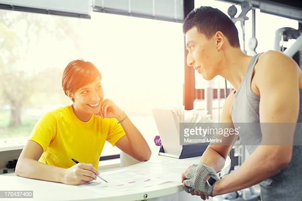 Couple discusses training plan in the gym