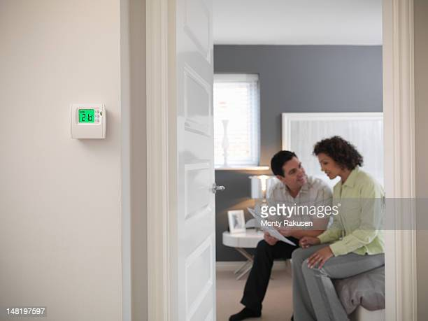 Couple discussing energy bills in bedroom of energy efficient house