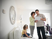 Couple discussing energy bills while daughter plays on sofa in living room