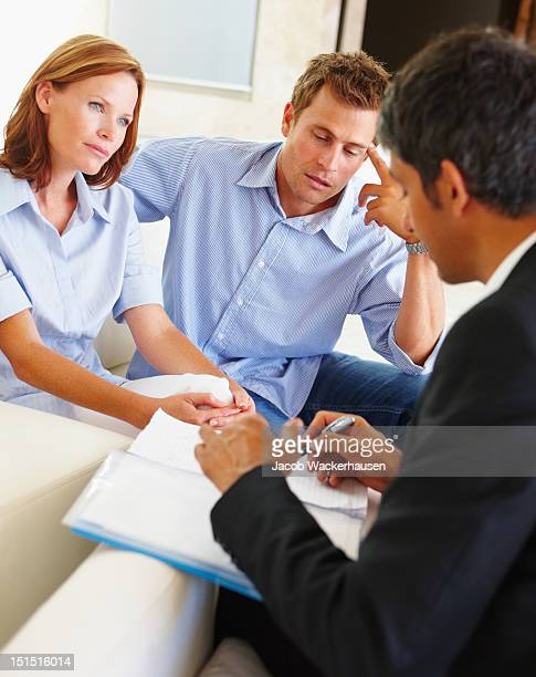 Couple discussing financial matter with bank executive