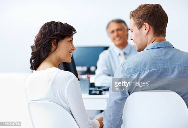 Couple discussing financial plans with advisor