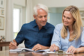 Mature couple doing family finances at home. Senior couple discussing home economics sitting at table. Happy couple sitting at home planning household financials.