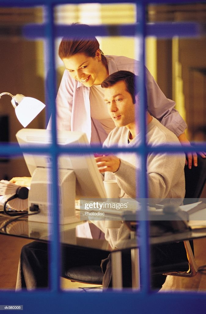 Couple discussing work at desk : Stock Photo