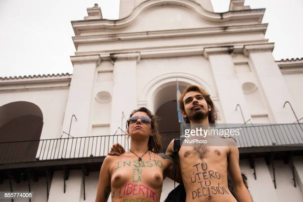 A couple display their bellies painted with legends reading quotYour uterus your decisionquot and quotI do insist in the freedom of choice over my...