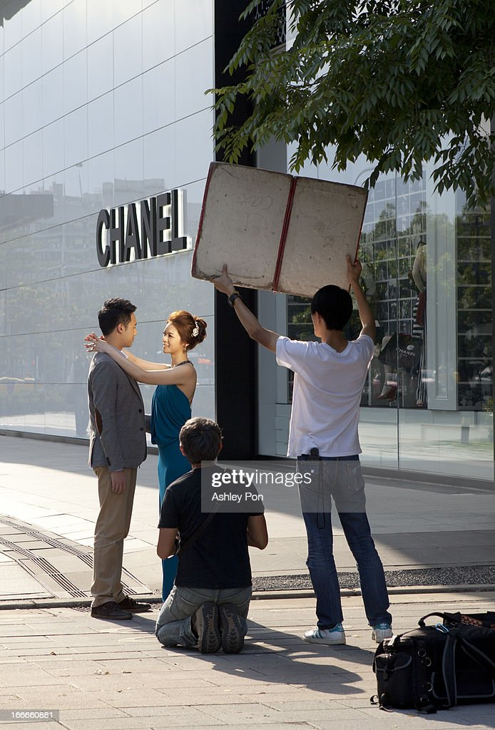A couple doing a wedding photoshoot is seen in front of a Chanel store in Taipei's Hsin-yi district on April 15, 2013 in Taipei, Taiwan.