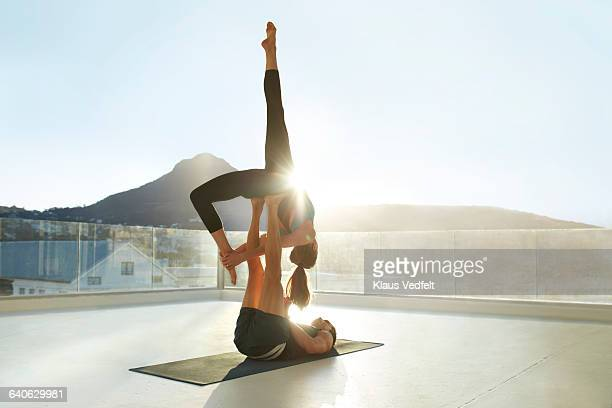 Couple doing acrobatic yoga on rooftop terrace