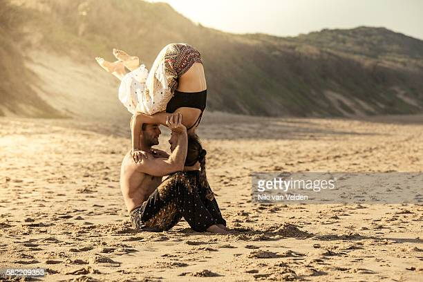 Couple doing Acroyoga on beach