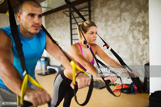 Couple doing arm exercises with suspension straps at gym.