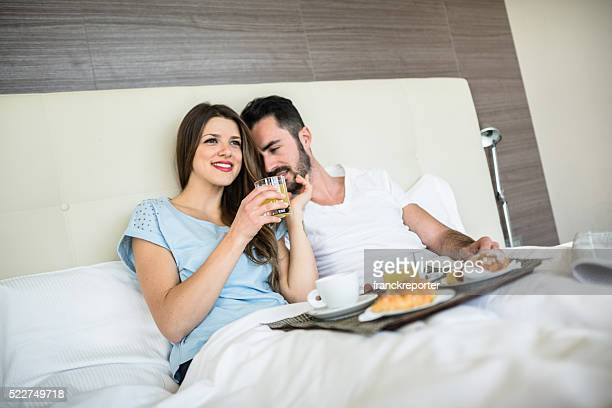 couple doing breakfast on the bed